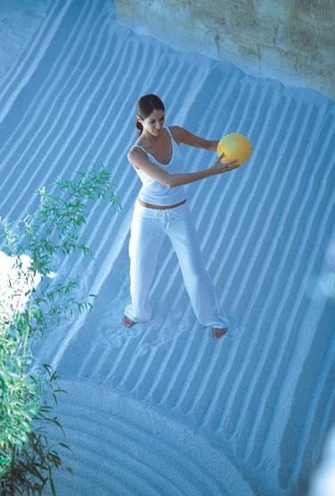 Femme pratiquant le gym-ball dans le sable, pilate