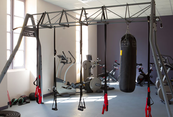 Salle de sport moderne avec sac de boxe, cage TRX et bikes